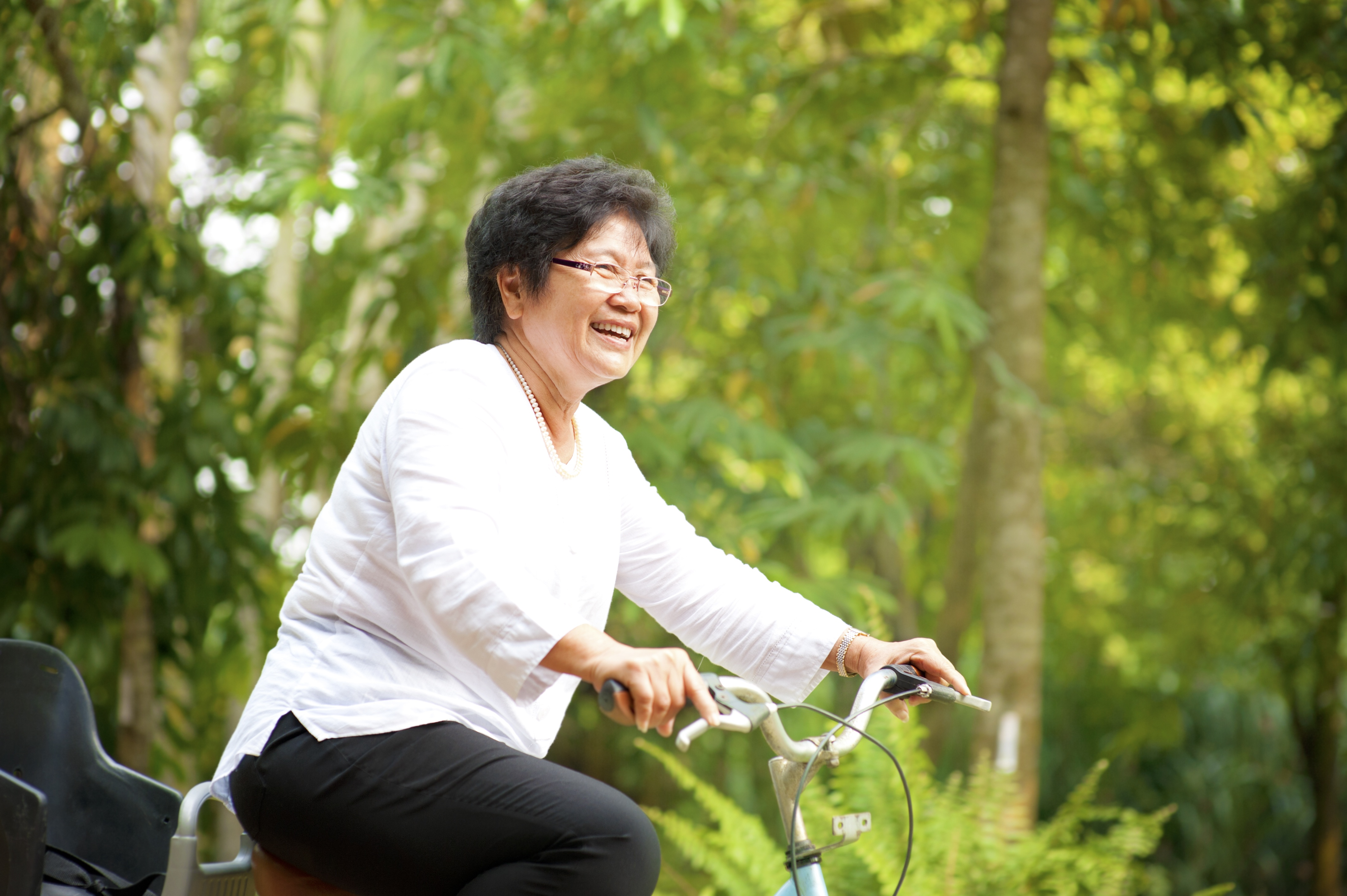 60s_senior_Asian_woman_riding_on_bicycle_outdoor_with_great_fun.jpg